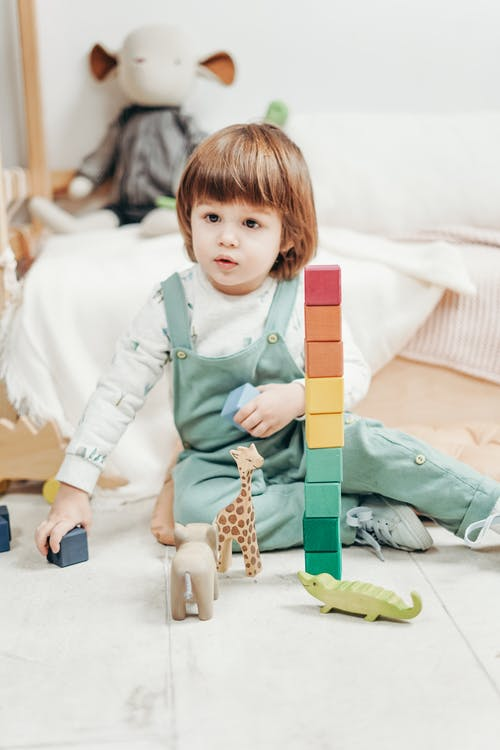 Child in White Long-sleeve Top and Dungaree Trousers Playing With Lego Blocks and Toys