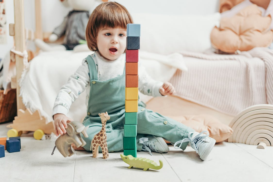 Child in White Long-sleeve Top and Green Dungaree Trousers Playing With Lego Blocks and Toys