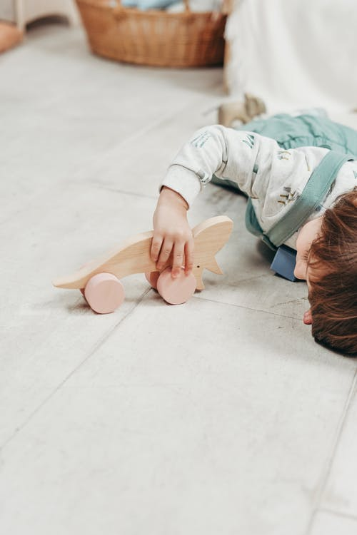 Child in White Long Sleeve Top and  Dungaree Trousers Lying Down Playing with Wooden Toy