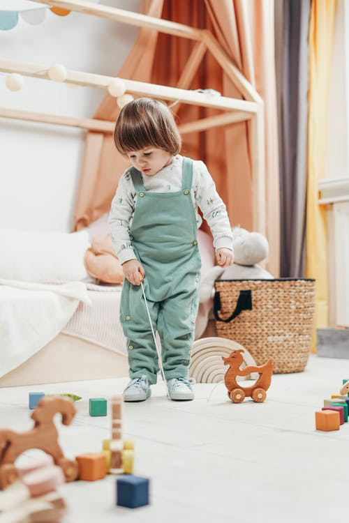 A Child Looking At The Toys On The Floor