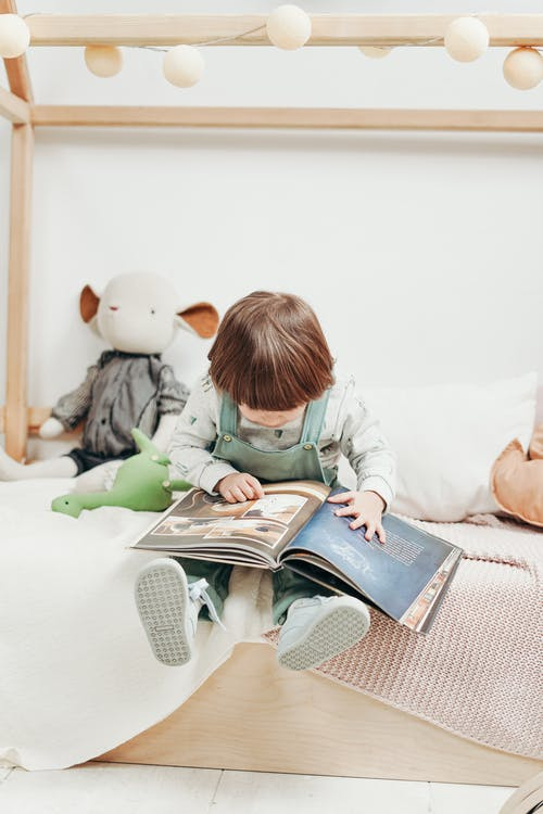 Child in White Long-sleeve Top and Dungaree Trousers Sitting on Bed Reading Book
