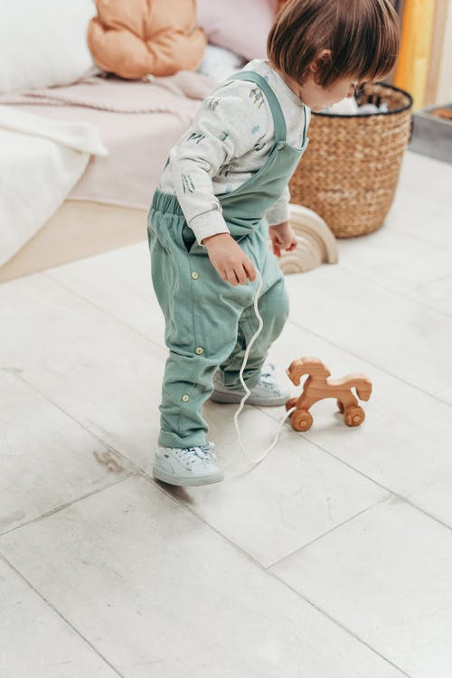 Child in White Long-sleeve Top and Dungaree Trousers Playing With Wooden Toy on White Floor