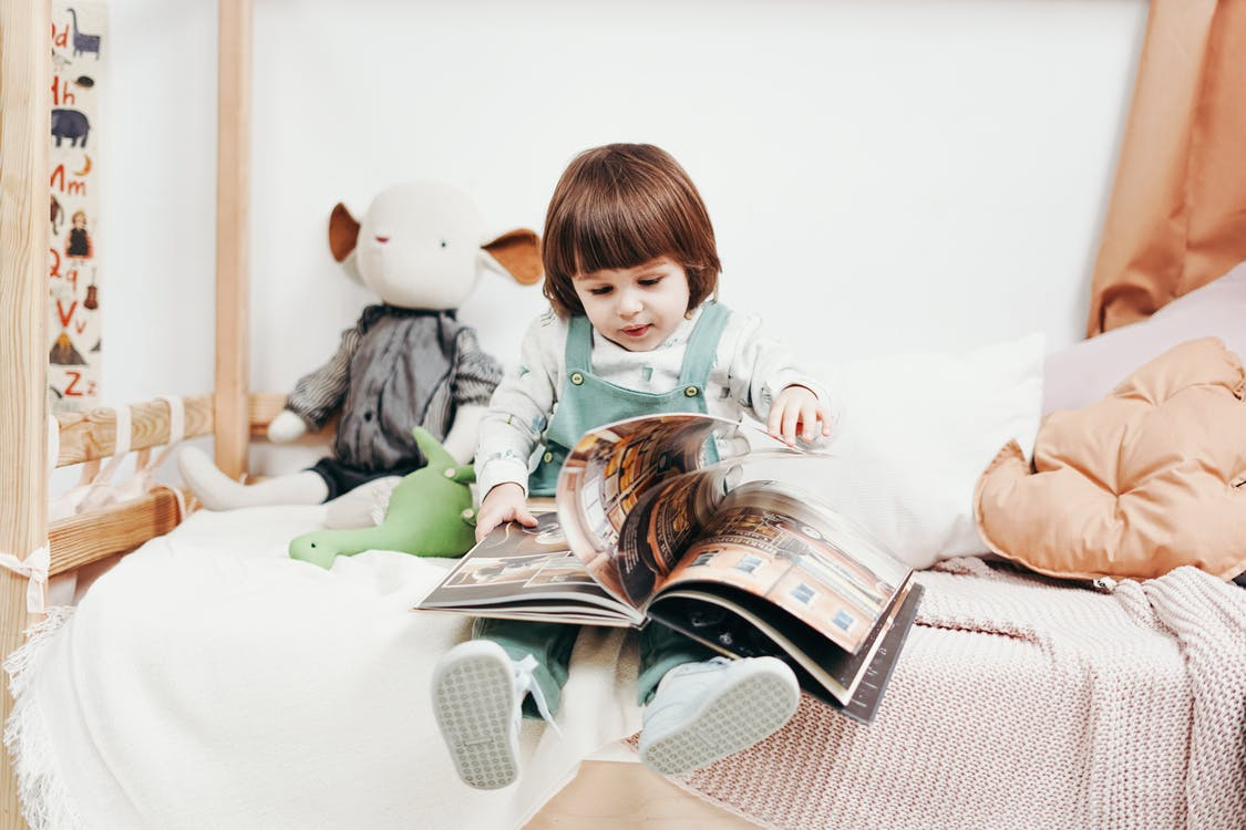 photo of a baby girl perusing a magazine