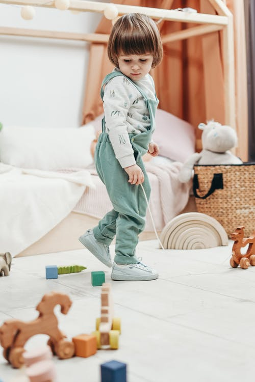 Child in White Long-sleeve Top and Green Dungaree Trousers Playing With Toys