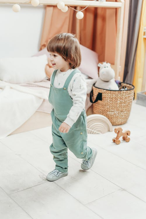 Child in White Long-sleeve Top and Green Dungaree Trousers Playing With Wooden Toy