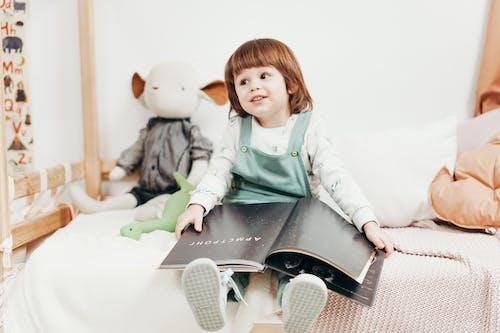 Trẻ Em Mặc áo Dài Tay Trắng Ngồi Trên Giường ôm Sách