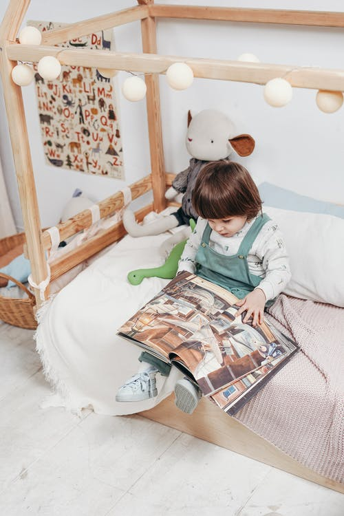 Child in White Long-sleeve Top Reading Book Sitting on Bed
