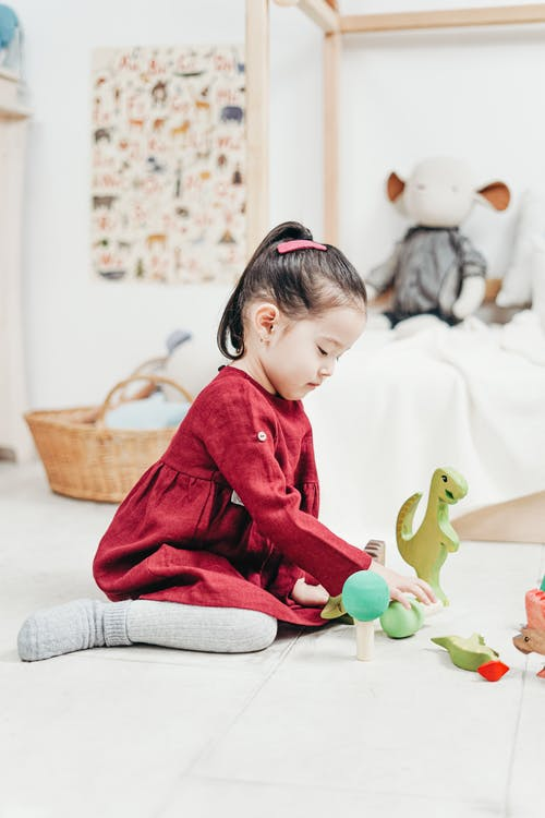 Girl in Red Long Sleeve Dress Sitting on White Floor Tiles Playing with Toys