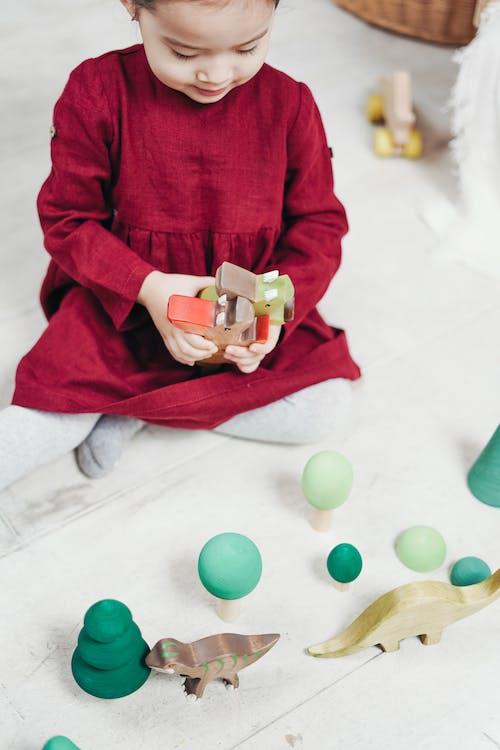 Meisje In Rode Jurk Met Lange Mouwen Zittend Op Witte Vloertegels Spelen Met Speelgoed