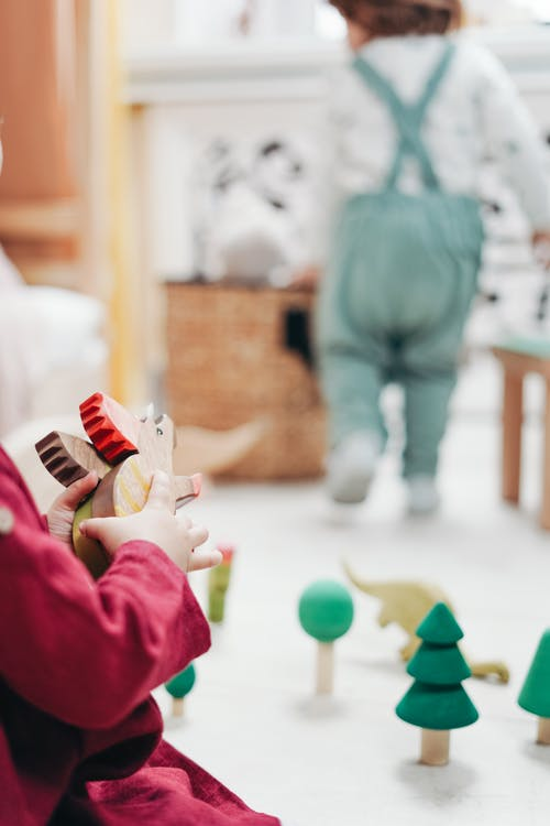 Child in Red Top Holding Wooden Toys