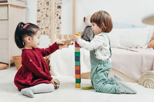Two Children Playing with Lego Blocks on Floor