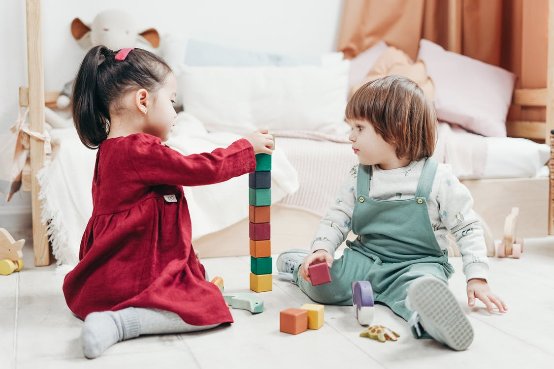 Children Sitting Down on the Floor Playing with Lego Blocks