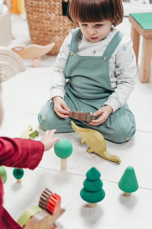 baby in Green Apron Holding Brown Wooden toy