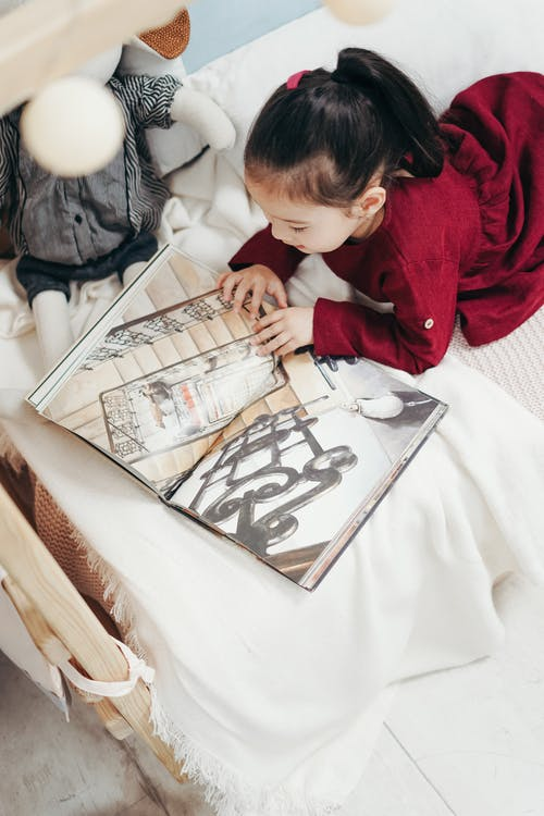 Girl in Red Long Sleeve Dress Reading Book