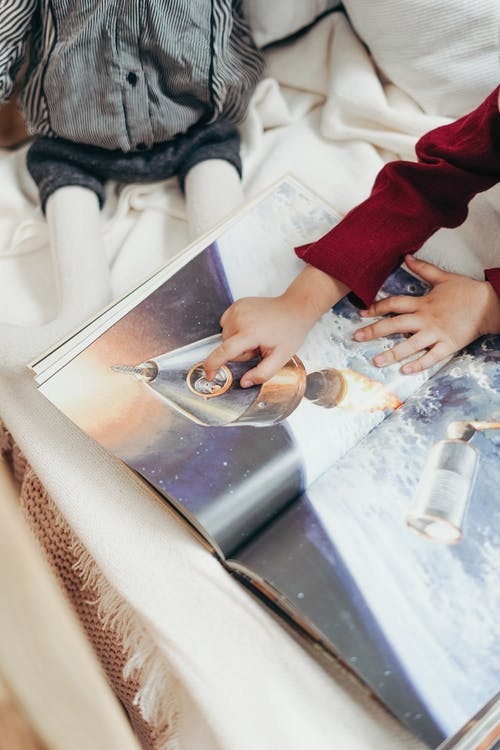 Child Hand Pointing to a Spaceship Illustrated on Book