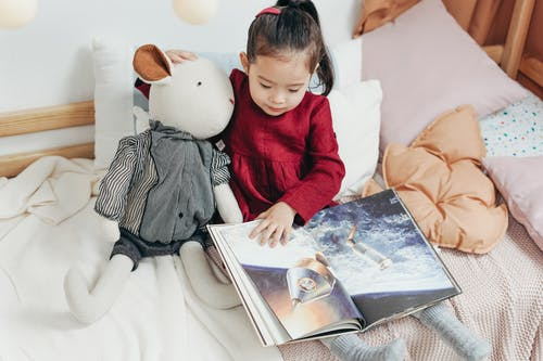 Girl in  Red Dress Sitting on Bed Reading Book