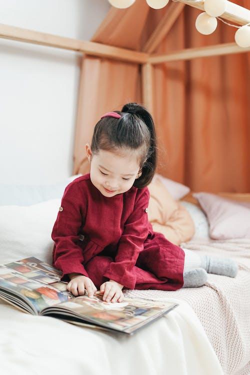 Ragazza In Vestito Rosso Che Si Siede Sul Libro Di Lettura Del Letto