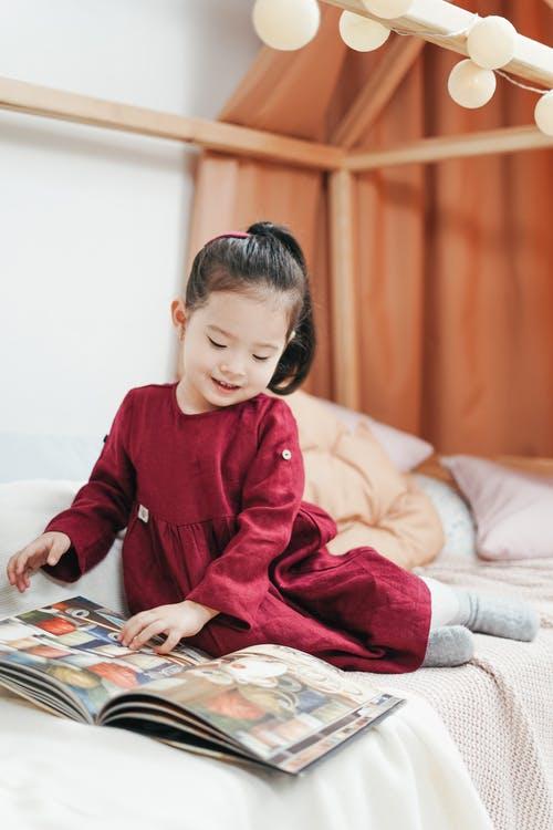 Girl in Red Dress Shirt Sitting on Bed Looking at Book