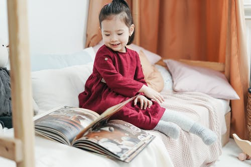Girl in Red Long Sleeve Dress Sitting on Bed Reading Book