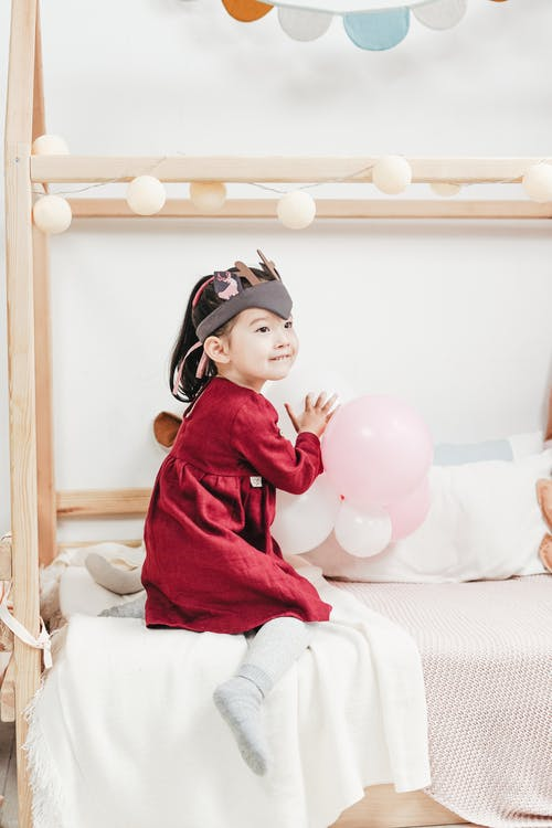 Girl in Red Long Sleeve Dress Sitting on Bed Playing with Balloons