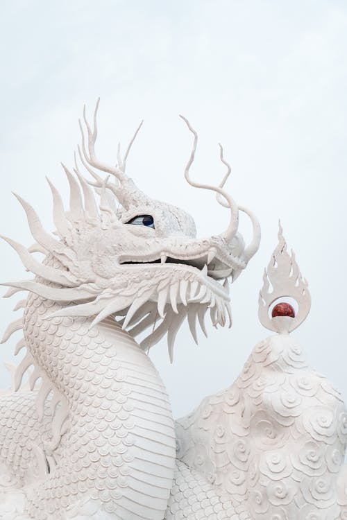 Sculpture of a White Dragon With Blue Background