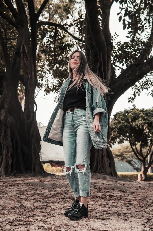 Photo of Standing Woman in Blue Denim Jacket and Jeans Posing With Trees in the Background
