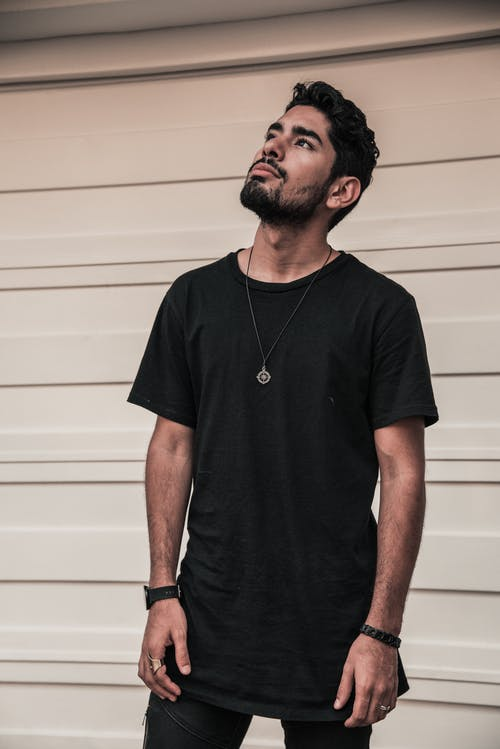 Photo of Man in Black Crew Neck T-shirt Standing Beside White Wall While Looking Up