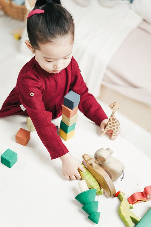 Girl in Red Dress Playing Wooden Blocks