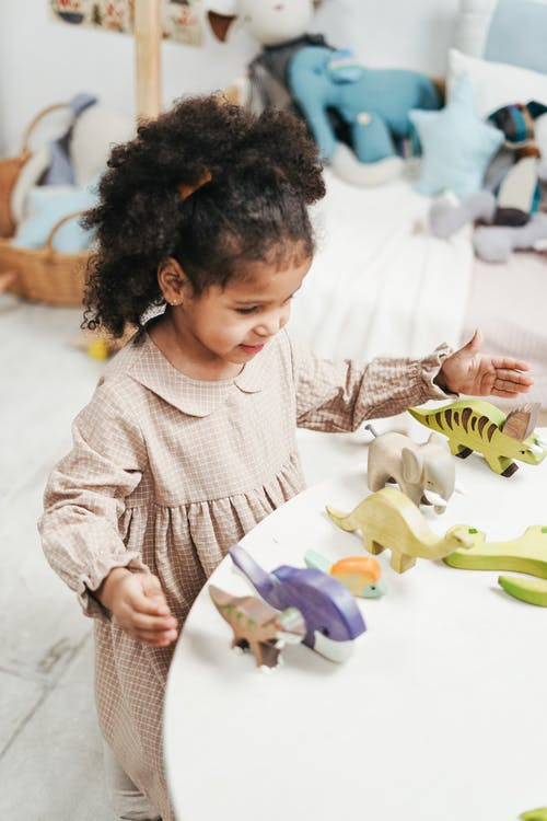 Selective Focus Photo of Young Girl Playing with Wooden Toys on White Table