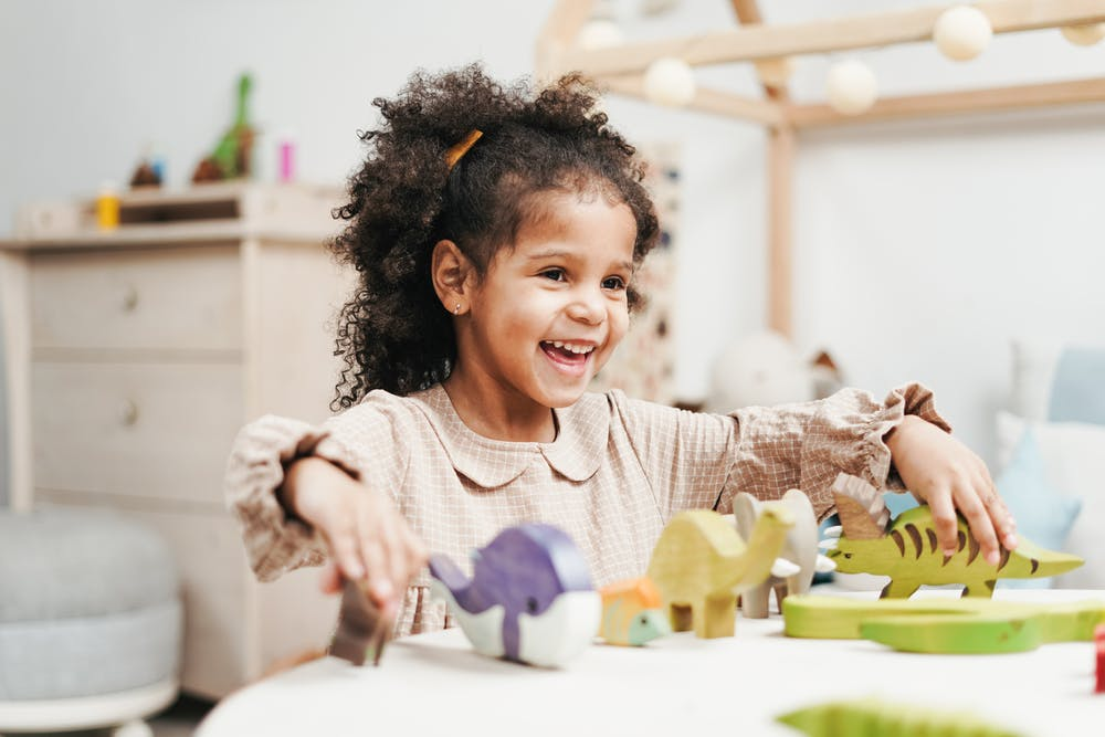 Little girl playing with wooden toys on a table. | Photo: Pexels