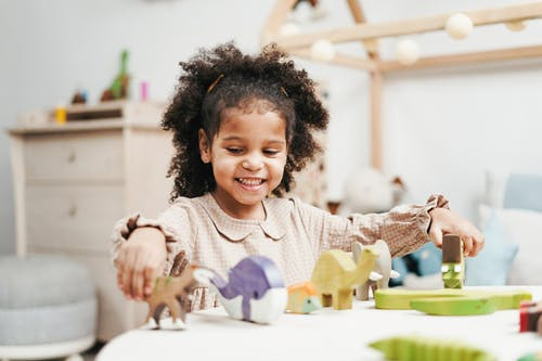 Selective Focus Photo of Smiling Young Girl Playing with Wooden Toys on White Table