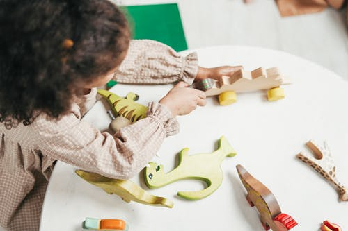 Overhead Photo of Young Girl Playing with Wooden Toys on White Table