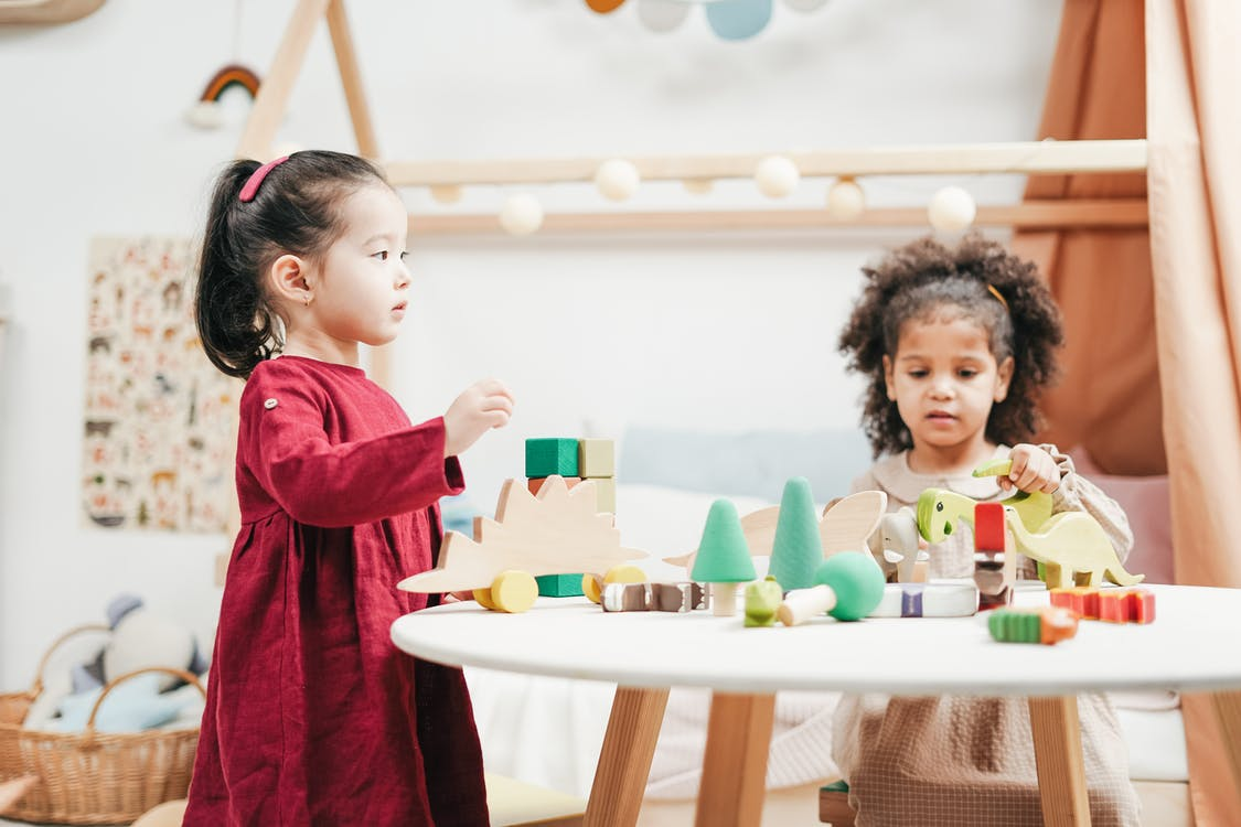 Two Children Playing A Wooden Toys