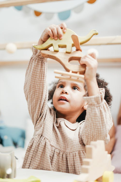 Girl in White and Brown Stripe Hoodie Raising Her Hands with Toys