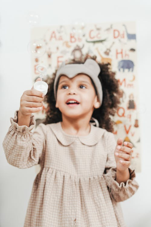 Girl in Brown Dress Playing Bubbles