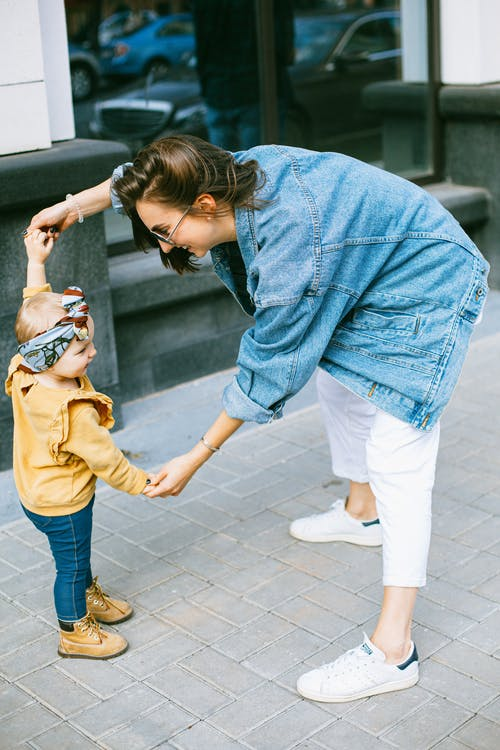 Woman in Blue Denim Jacket and white Pants Holding Girl in blue Pants