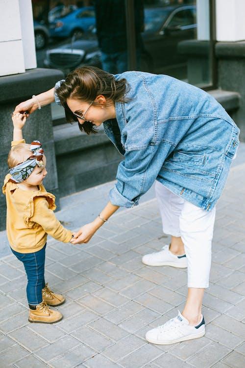 Donna In Giacca Di Jeans Blu E Pantaloni Bianchi Che Tiene Ragazza In Pantaloni Blu