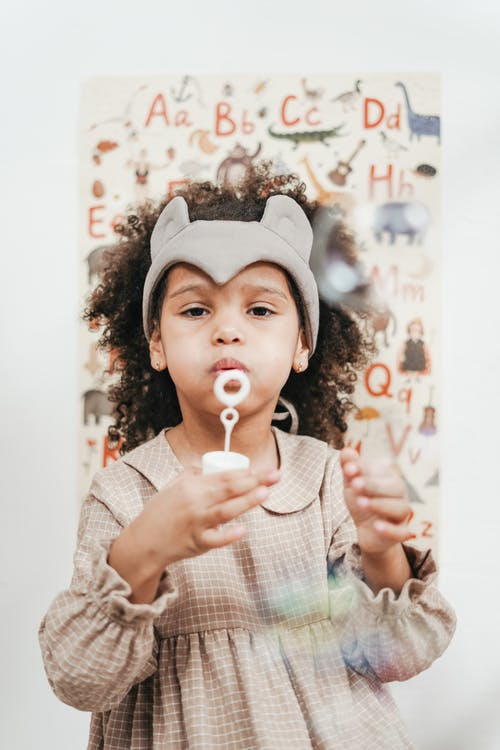 Girl Wearing Brown Dress While Blowing Bubbles