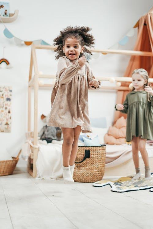 Girl Wearing Brown Dress While Jumping