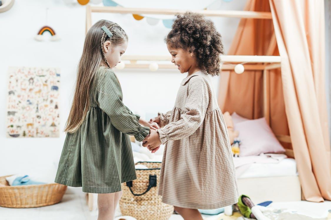 Foto Van Meisjes Dragen Jurk Terwijl Hand In Hand