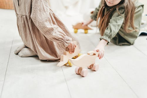 Photo of Two Girls Playing With Wooden Toys