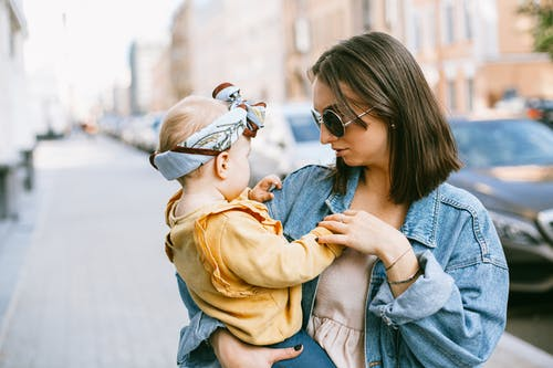 Woman in Blue Denim Jacket Carrying Baby