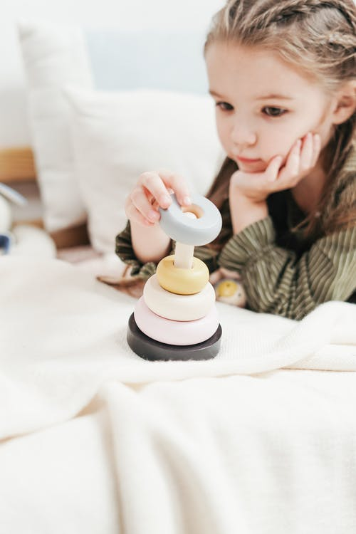 Girl Playing with Wooden Stacking Toy