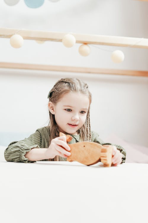 Girl Holding Wooden Toy