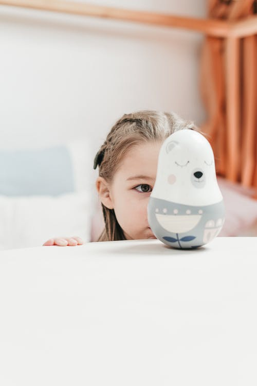Girl staring at a White and Blue Ceramic Bird Figurine