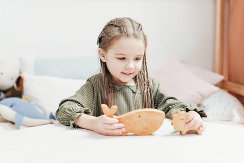 Photo of Girl Playing With Wooden Toys