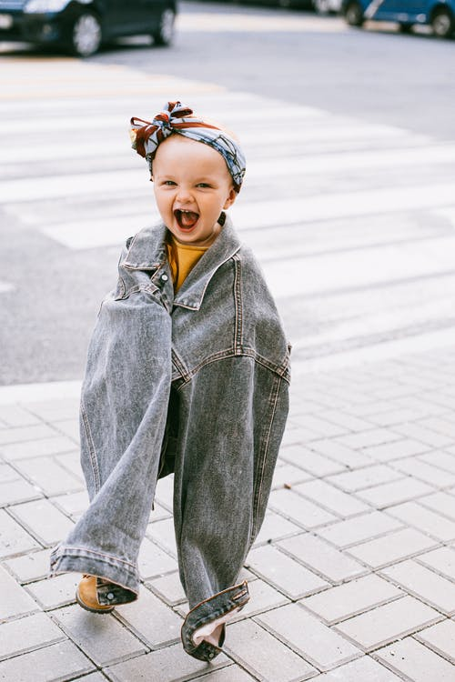 Smilling Baby in an Oversize Denim Jacket