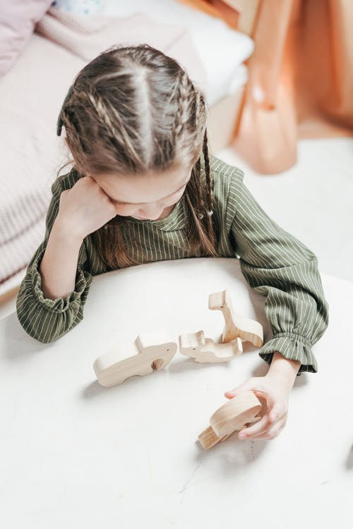A Girl Playing a Wooden Toy at the Table