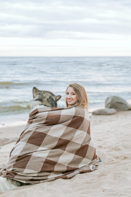 Woman And A Siberian Husky In A Seashore