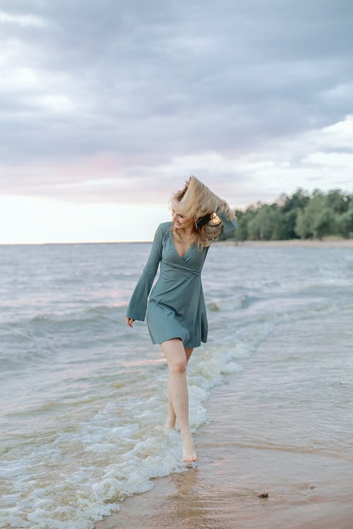 Woman in Green Long Sleeve Dress Standing on Beach